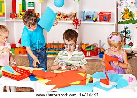 Child boy cutting out scissors paper in preschool.