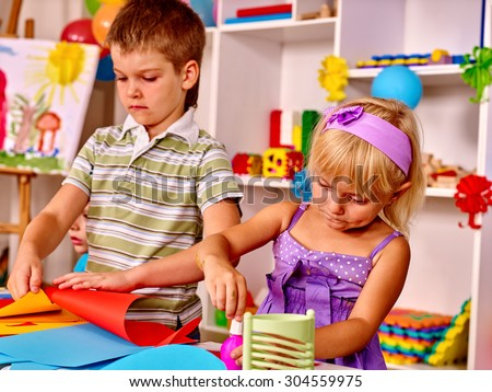 Child boy cutting out scissors paper in preschool. Education and development. - stock photo