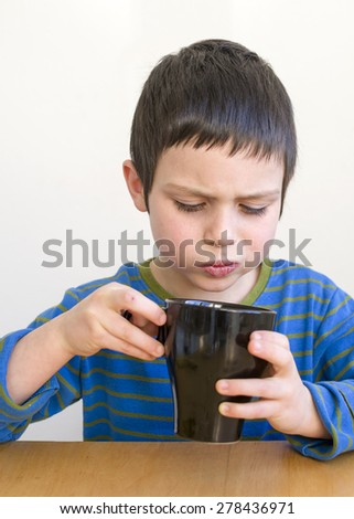 Child boy drinking hot cup of tea at the table - stock photo