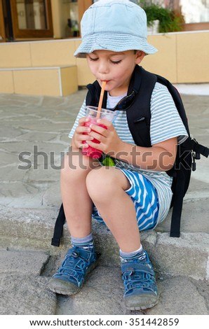 Child boy  drinking ice slush drink from a plastic cup with straw at the street in summer