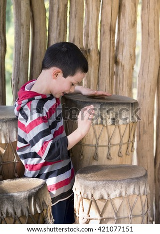 Child boy drumming traditional african drums - stock photo