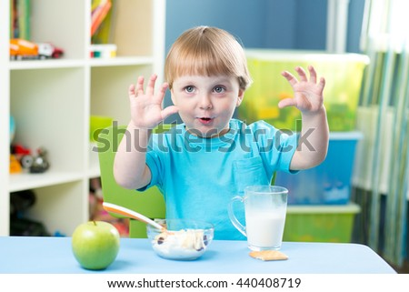 child boy eating apple at dinner in nursery at home