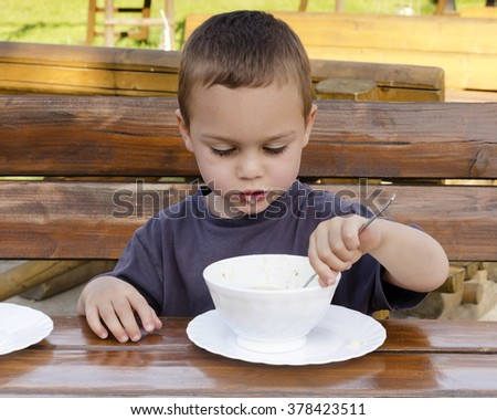 Child boy eating soup from a bowl at outdoor table in a garden or restaurant