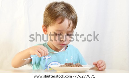 Child boy eats food with a fork from a plate.