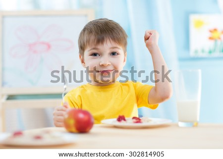 child boy eats healthy food showing his strength indoors - stock photo