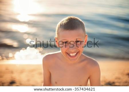 child boy happy smile with teeth brace, shallow DOF, sunset lighting - stock photo