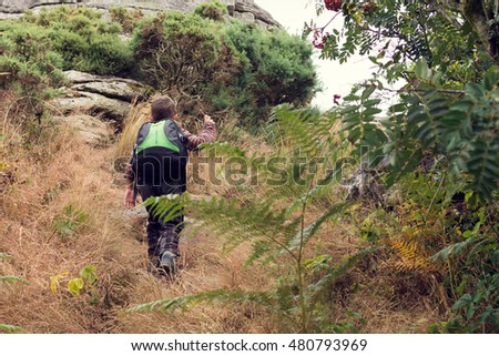 Child boy hiking in the nature heading up hill toward a rock, Dartmoor, England
