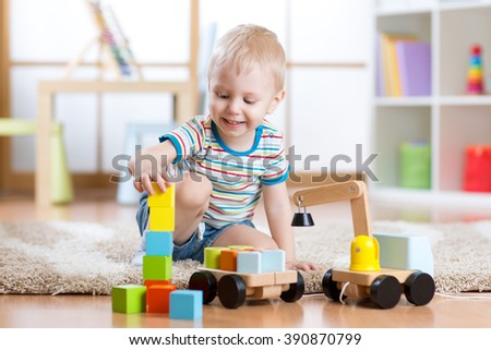 Child boy is happy to play toy building blocks and loader car - stock photo