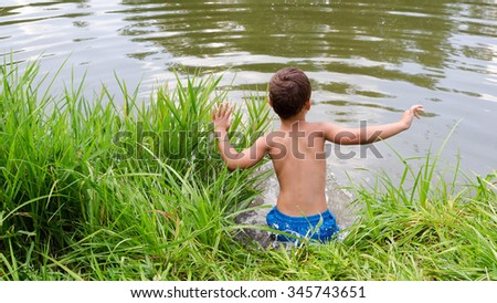 Child boy jumping into water of a lake or pond from grass bank. - stock photo