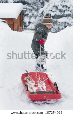 Child boy or girl pulling a sledge in fresh snow in winter - stock photo