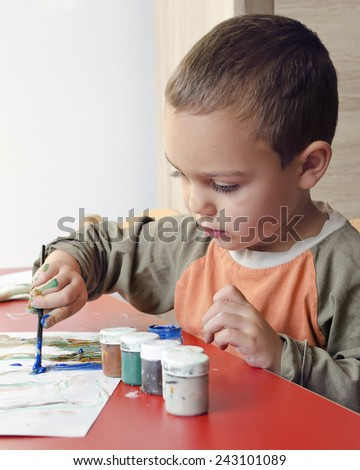 Child boy painting a picture with brush and colors at home or school nursery. - stock photo