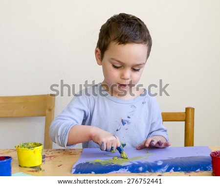 Child boy painting a picture with with finger colors at home or school nursery. - stock photo
