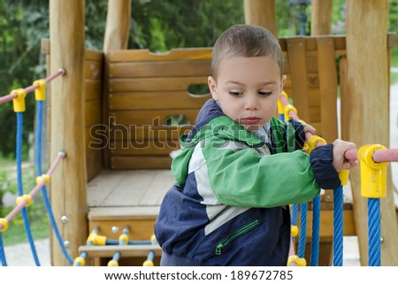 Child boy playing at modern playground on rope bridge - stock photo