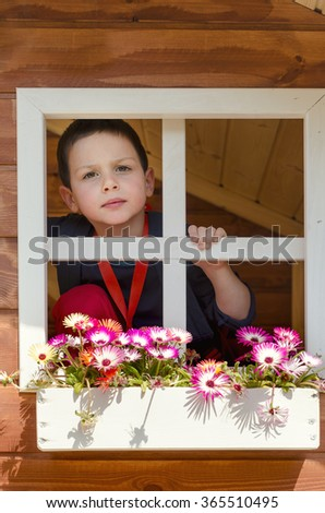Child boy playing in wooden garden house or shed  - stock photo