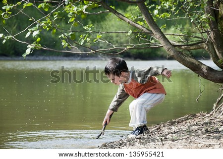 Child boy playing with a stick on the edge of the lake or a river in the nature. - stock photo