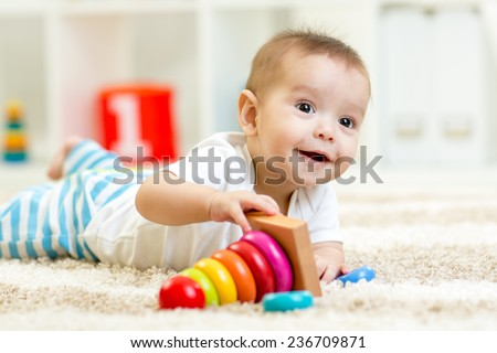 Child boy playing with toy indoors at home - stock photo