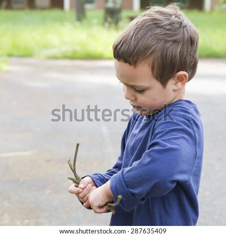 Child boy playing with twigs in park or garden - stock photo