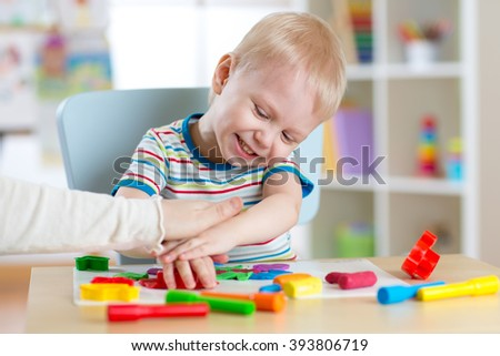 Child boy plays with clay dough, education and daycare concept - stock photo