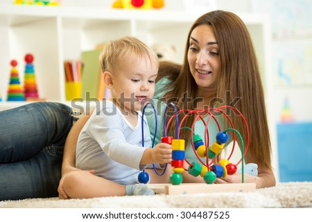 Child boy plays with educational toy in nursery at home. Happy mother looking at her smart son. - stock photo