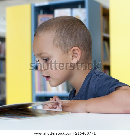 Child boy reading a book in a public library room.  - stock photo