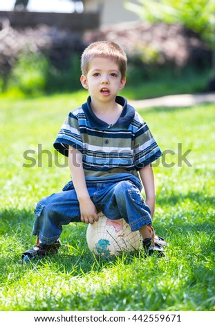 child boy sitting on a  ball in a grass outdoor - stock photo