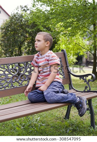 Child boy sitting on a bench in park. - stock photo