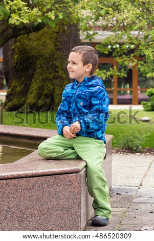 Child boy sitting on a fountain pond in a park or garden.