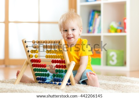 child boy smiling and playing with counter toy at home - stock photo