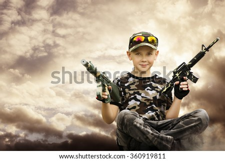 Child Boy Soldier, Toy Automatic Guns, Kid in Camouflage Play Army Game - stock photo