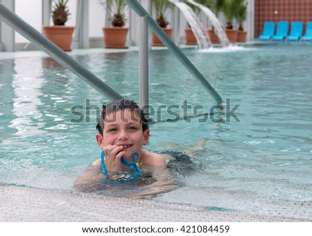 Child boy swimmer at the edge of swimming pool at leisure or holiday resort - stock photo