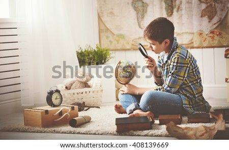 child boy teenager studying a map of the world, globe, geography, dreams of travel - stock photo