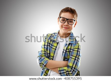 child boy teenager with glasses on a gray background