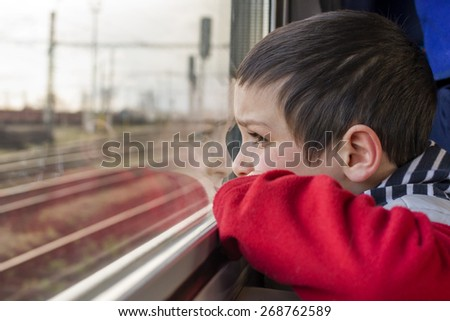 Child boy traveling by train and looking from a window. - stock photo