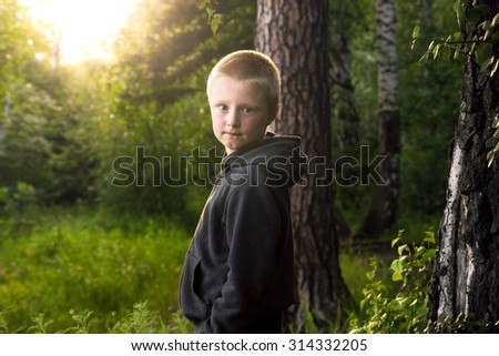 Child (boy) walking alone in green forest - stock photo