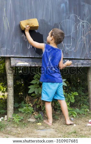Child boy wiping blackboard in outdoor forest school classroom, education concept. - stock photo