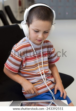 Child boy with headphones listening music or audio in a classroom or library room. - stock photo