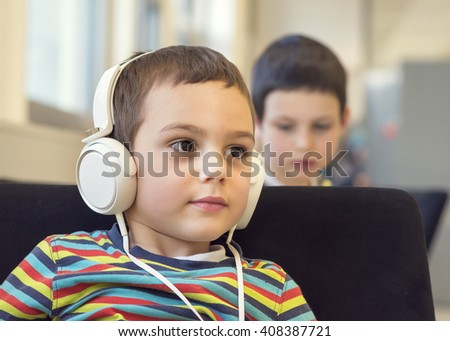 Child boy with headphones listening music or audio in a classroom or library room - stock photo