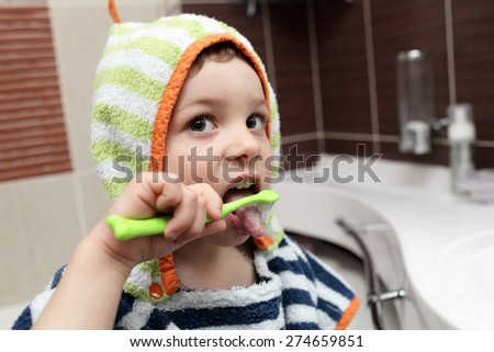 Child brushing his teeth in the bathroom - stock photo