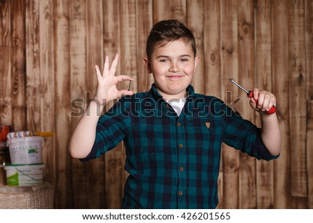 child builder for construction  work concept, funny boy, builder shows a screwdriver, sign of cool - stock photo