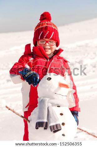 Child building a snowman - stock photo