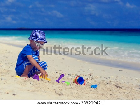child building sandcastle on tropical beach