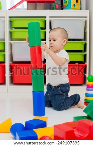 child builds a tower of cubes  - stock photo