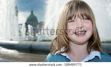 Child by fountain in copenhagen. Boy in amaliehaven by amalienborg with the marble church in the background - stock photo