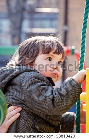 Child, carefully guarded a hand the grown man perches upstairs on a playground - stock photo