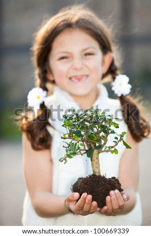 child caring for the environment (focus on tree) - stock photo