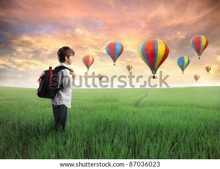 Child carrying a backpack standing on a green meadow with hot-air balloons in the background