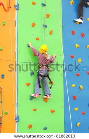 Child climbing on a climbing wall, outdoor - stock photo