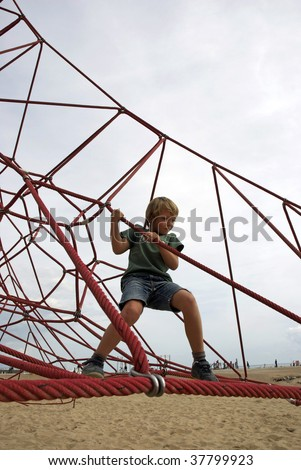Child climbing on a net of ropes - stock photo