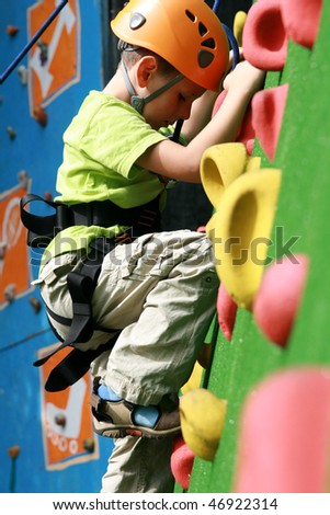 child climbing on a wall in an outdoor climbing center - stock photo
