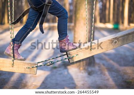 Child climbing on high rope park - stock photo
